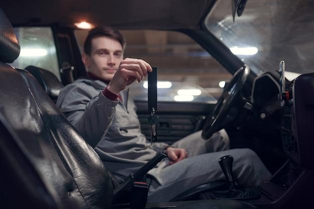 Foto del lato dell'autista che tiene le chiavi seduto in un'auto nera