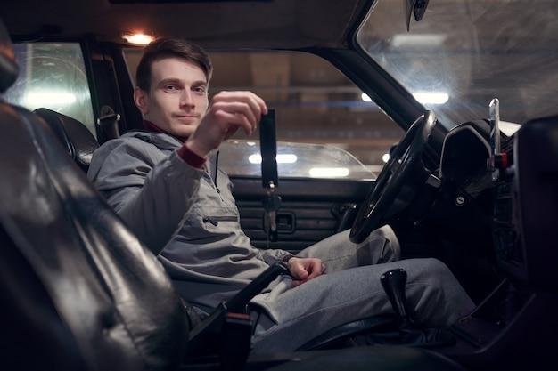 Foto del lato dell'autista che tiene le chiavi seduto in macchina