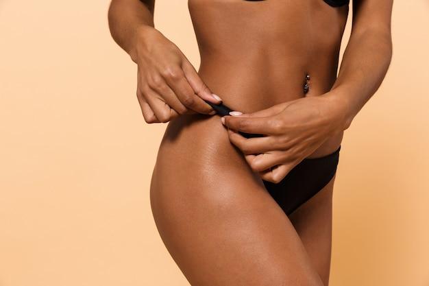 Foto di donna magra che indossa lingerie nera, in piedi isolato sul muro beige
