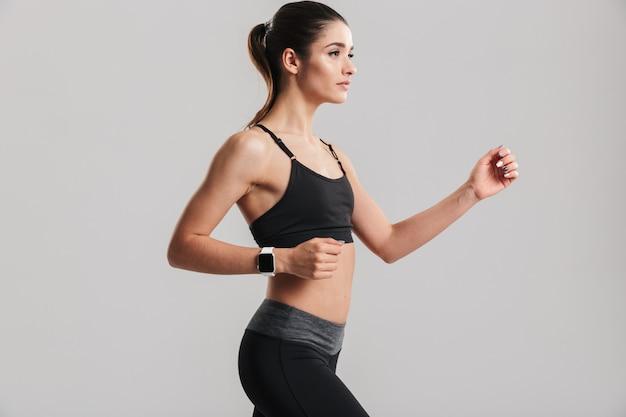 Foto della donna esile di forma fisica che corre o che risolve con l'orologio sul polso, isolata sopra la parete grigia