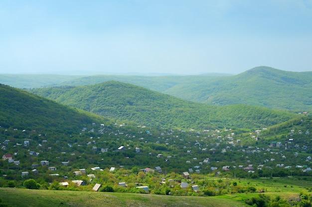 Foto di un piccolo villaggio situato tra le montagne un sacco di piante verdi intorno