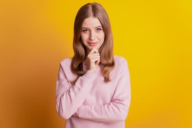 Foto del mento del dito della ragazza intelligente intelligente su sfondo giallo