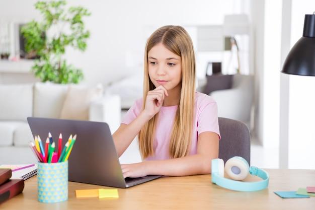 Foto di una ragazza di livello intelligente che si siede al tavolo scrivania studia l'uso remoto del computer portatile ha una lezione compito soluzione di brainstorming risposta tocco mano mento in casa al chiuso
