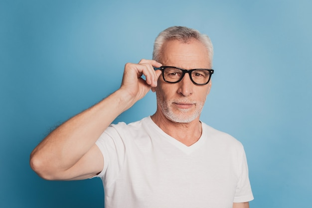 Foto di un uomo anziano intelligente che tocca gli occhiali isolati su sfondo blu