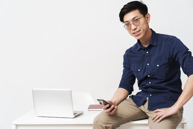 Foto di un uomo d'affari asiatico sorridente che indossa occhiali seduto al tavolo e tiene in mano lo smartphone mentre lavora con il computer portatile in ufficio isolato su un muro bianco
