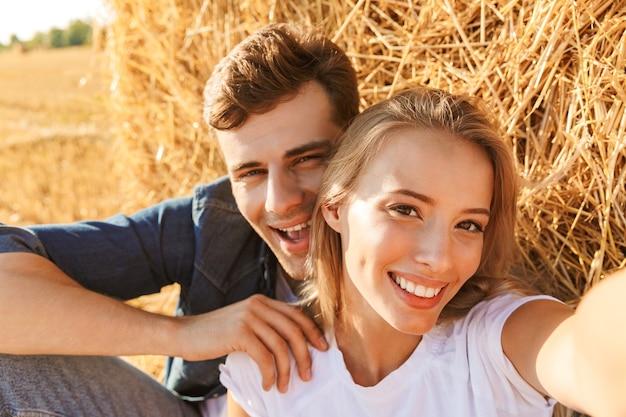 Foto di coppia sorridente uomo e donna che prendono selfie seduti sotto un grande pagliaio in campo dorato, durante la giornata di sole