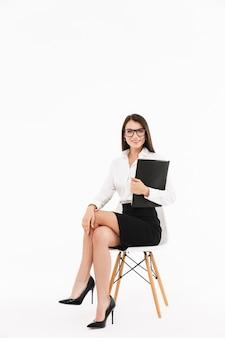 Foto di una donna d'affari lavoratrice sorridente vestita con abiti formali che tiene in mano un rilegatore con documenti mentre è seduta su una sedia da ufficio isolata su un muro bianco