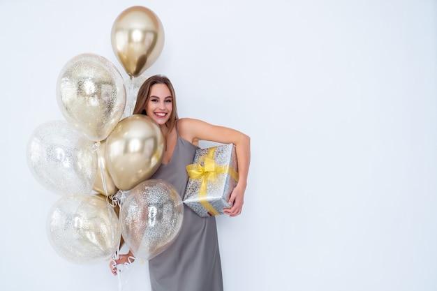 La foto di una ragazza sorridente tiene in mano una grande confezione regalo avvolta e molti palloncini d'aria sono venuti alla celebrazione della festa