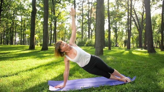 Foto di una donna sorridente felice di 40 anni che fa esercizi di yoga sul tappetino fitness nella foresta. armonia della natura umana. persone di mezza età che si prendono cura della salute mentale e fisica