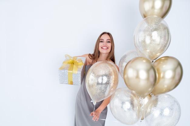 La foto di una donna sorridente tiene in mano una grande confezione regalo avvolta e molti palloncini d'aria sono venuti alla celebrazione della festa