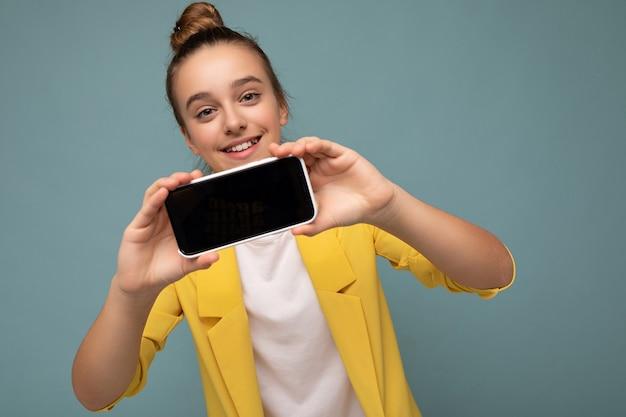 Foto della bella ragazza teenager sorridente che indossa in piedi alla moda casual isolato sopra