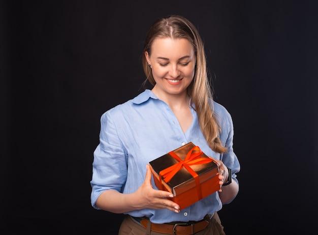 Foto di una giovane donna d'affari sorridente che tiene in mano una scatola regalo rossa per natale