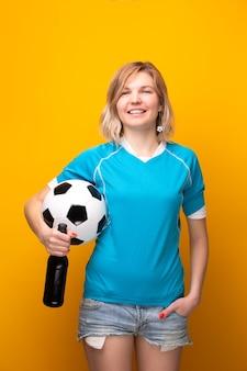 Foto di una bionda sportiva che tiene in mano tra la palla e una bottiglia di alcol su sfondo arancione