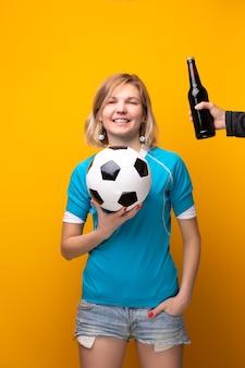 La foto della bionda sportiva con le braccia incrociate sta scegliendo tra palla e bottiglia di alcol su sfondo arancione