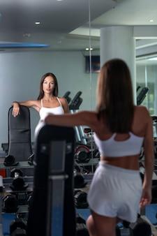 Foto di una ragazza sportiva vestita con una maglia bianca, pantaloncini sportivi bianchi si guarda allo specchio in palestra. foto dal retro del modello. palazzetto dello sport.