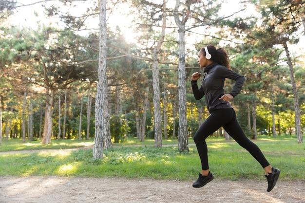 Foto di una sportiva 20s in tuta nera e cuffie che si allenano mentre attraversano il parco verde