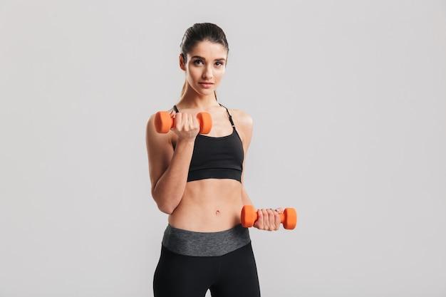 Foto dell'allenamento sportivo della donna con le piccole teste di legno, isolata sopra la parete grigia