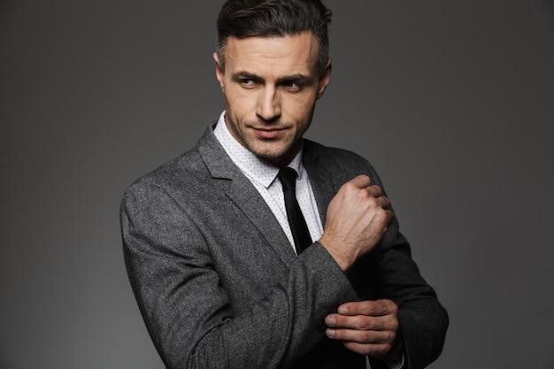 Foto di elegante uomo che indossa tailleur alla ricerca da parte, mentre fissare gemello o pulsante sulla manica della giacca, isolato su muro grigio