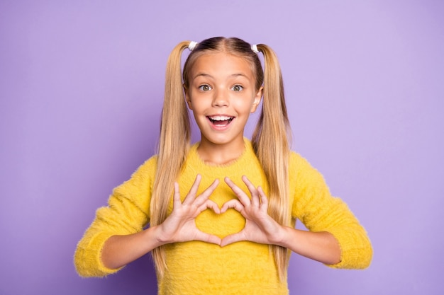 Foto della ragazza positiva allegra alla moda elegante che mostra il segno di forma del cuore con le emozioni sul fronte isolato nel muro di colore viola pastello maglione giallo