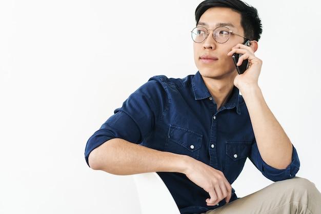 Foto di un uomo d'affari asiatico di successo che indossa occhiali seduto su una sedia e parla su smartphone mentre lavora in ufficio isolato su un muro bianco