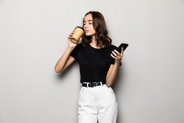 Foto di una donna di successo in abbigliamento formale in piedi con lo smartphone e il caffè da asporto nelle mani isolate su grigio