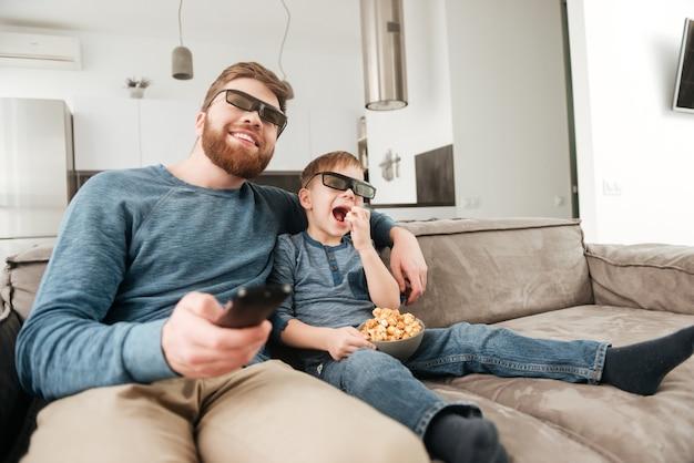 Foto di padre felice sorpreso che tiene il telecomando mentre guarda la tv con il suo piccolo figlio carino usando occhiali 3d che tengono popcorn.