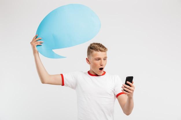 Foto del ragazzo sorpreso dei pantaloni a vita bassa che tiene la bolla di pensiero in bianco sopra la sua testa e che posa con la bocca aperta con il telefono cellulare a disposizione isolato su bianco
