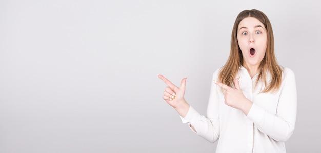 La foto della donna sorpresa indica in alto, ha un'espressione facciale scioccata, indossa una maglietta bianca contro il bianco.