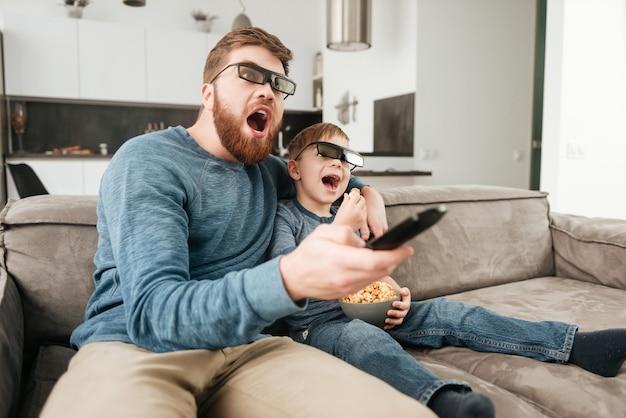 Foto di un giovane padre sorpreso che tiene il telecomando mentre guarda la tv con il suo piccolo figlio carino che usa occhiali 3d con in mano dei popcorn.