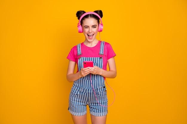 Foto di una giovane donna che tiene il telefono ascolta la musica degli auricolari canzone giovanile su sfondo giallo