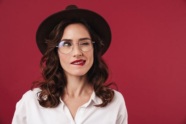 La foto di una giovane bella donna pensante in posa isolata sul muro rosso si morde il labbro.