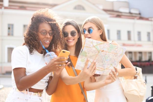 Foto di tre ragazze che si godono le visite turistiche all'aperto. belle turiste che esplorano la città con la mappa.