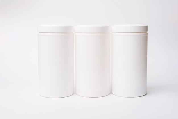Foto di un mockup di tre contenitori bianchi su sfondo bianco