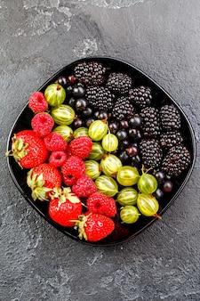 Foto sulla parte superiore di more, fragole, lamponi, uva spina, ribes nero su piastra nera su superficie vuota nera