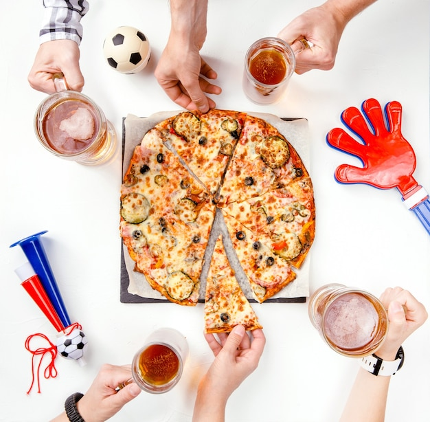 Foto in alto delle mani di tifosi di calcio con boccali di birra, pizza al tavolo bianco con pallone da calcio, pipa