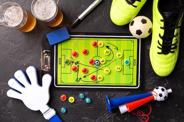 Foto sopra due boccali di birra schiumosa, calcio balilla, palla, scarpe da calcio, pipa, sonaglio sul tavolo nero