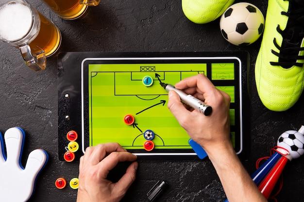 Foto sopra due boccali di birra schiumosa, calcio balilla, palla, scarpe da calcio, pipa, giocattoli a cricchetto, mani umane, schema di disegno sul tavolo bianco