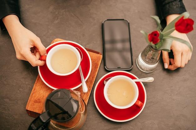 Foto vista dall'alto di mani femminili su sfondo di legno con tazza, teiera con tè e smartphone