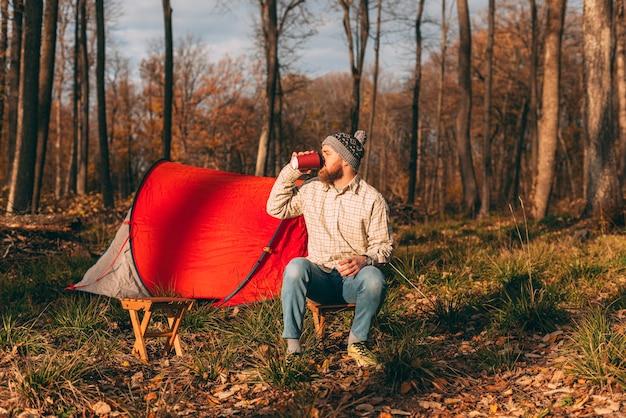 Foto di uomo barbuto viaggiatore seduto vicino alla tenda da campeggio, bevendo caffè mattutino