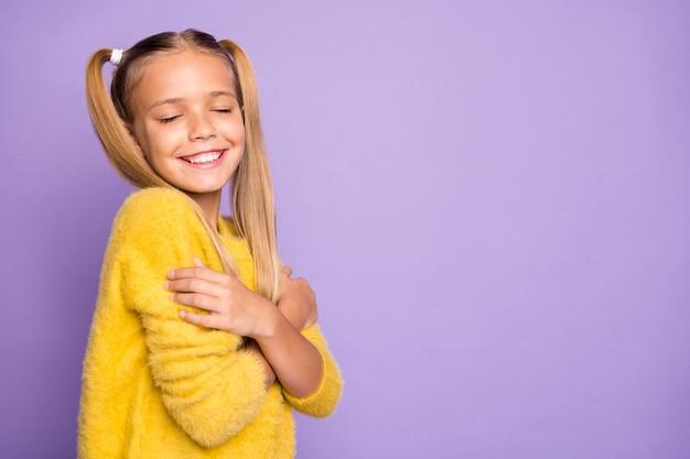 Foto della ragazza radiosa dentata allegra alla moda che si abbraccia la parete di colore viola pastello isolata confortevole