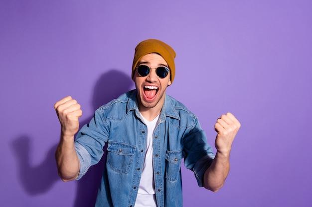 La foto del ragazzo alla moda bianco attraente bello felicissimo che indossa la camicia di jeans che si rallegra con le vendite ha iniziato a fare pugni mostrando il suo potere isolato su sfondo viola di colore vivido