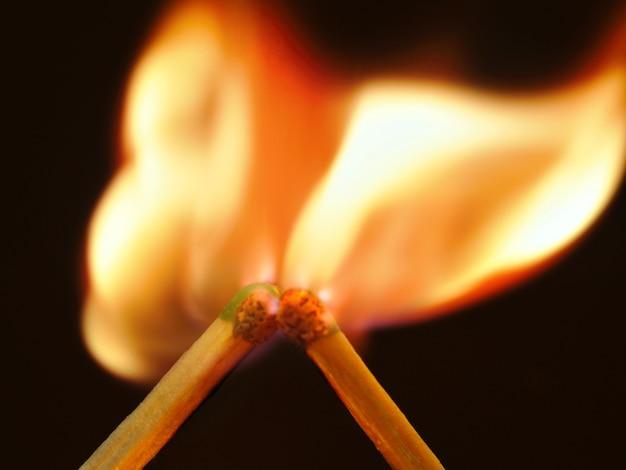 La foto due fiammiferi adiacenti bruciano intensamente. muro scuro, fiamma brillante