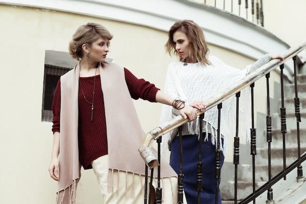 Foto di due belle donne in posa su una scala