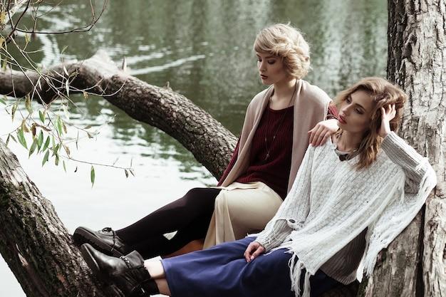Foto di due belle donne in posa su un albero vicino al lago.