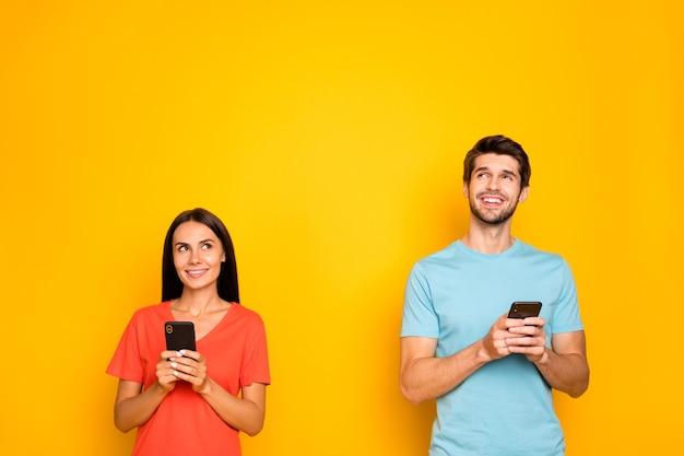 Foto di due divertenti guy lady persone coppia tenere telefoni braccia alzando lo sguardo spazio vuoto hanno creativo post testo idea indossare casual blu arancione t-shirt isolato giallo parete di colore