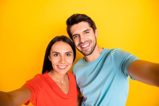 Foto di due simpatiche coppie di persone che fanno selfie carini che registrano video per il nuovo blog di social network indossano magliette arancioni blu casuali isolate muro di colore giallo