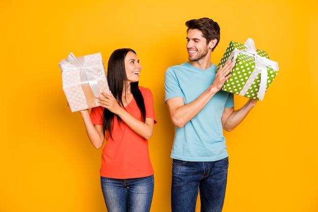 Foto di due simpaticoni lady persone che si tengono per mano grandi giftboxes guardando gli occhi grati indossare casual trendy blu arancione t-shirt jeans isolato giallo parete di colore