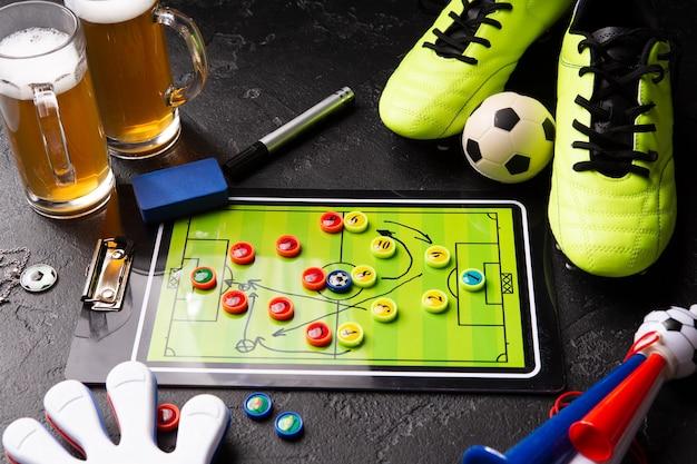 Foto di due boccali di schiuma di birra, calcio balilla, palla, scarpe da calcio, tubo, giocattolo sonaglio sulla tavola nera