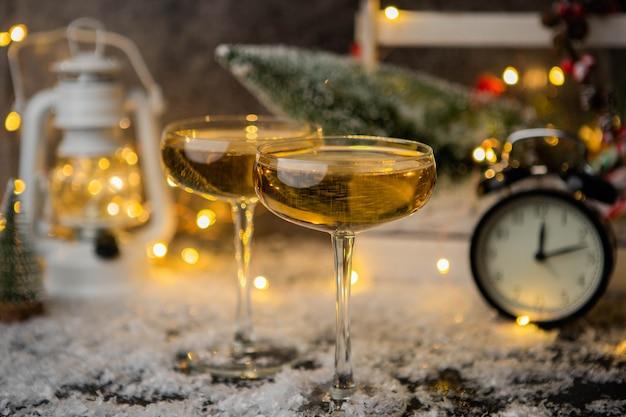 Foto di due bicchieri di vino sulla neve del tavolo con albero di natale, lanterna, orologio