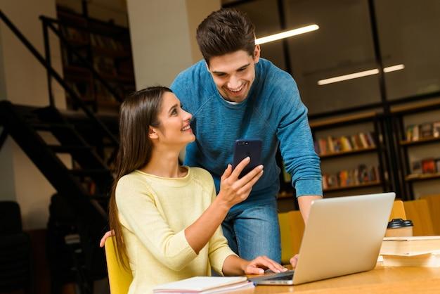 Foto di una coppia di amici di due giovani studenti in biblioteca a fare i compiti studiando leggere e utilizzando computer portatile e telefono cellulare.